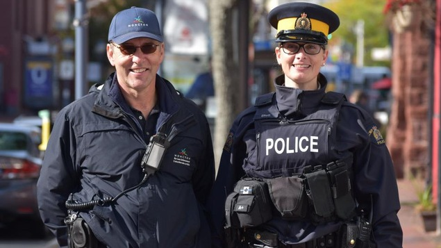 Un homme et une femme en uniforme côte à côte sur un trottoir.