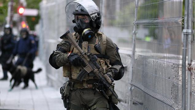 Un policier transportant une arme d'assaut dans ses mains monte la garde devant une clôture grillagée. Il porte un uniforme de couleur kaki, un casque de protection noir muni d'une visière, un masque à gaz, des jambières et des protège-coudes. À l'arrière-plan, on aperçoit deux autres policiers. L'un d'eux tient un chien en laisse.