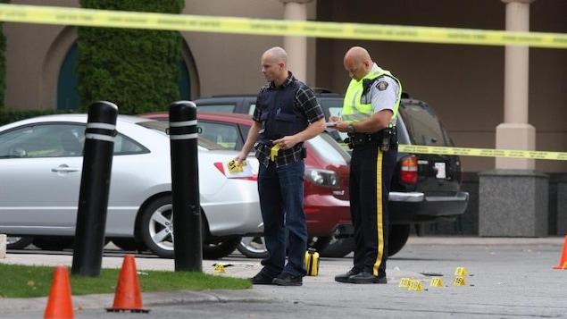 Deux policiers placent des marqueurs sur une scène de crime; trois voitures sont garées juste derrière eux et sur le sol se trouvent des marqueurs numérotés.