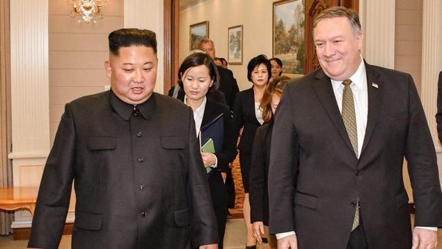 Deux hommes marchent côte à côte dans un riche décor, suivi d'une délégation d'une dizaine de personnes.