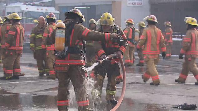 Un pompier qui arrose un autre pompier pour décontaminer sa combinaison sur le site d'un incendie à Montréal