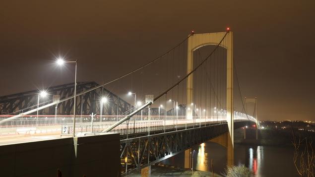 Le pont Pierre-Laporte, vu de la Rive-Nord, la nuit. Les phares du trafic automobile forment des traits lumineux grâce à l'exposition longue.