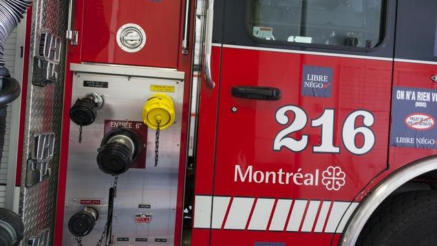 Détail de la portière d'un camion de pompiers de Montréal arborant des autocollants de revendications syndicales.