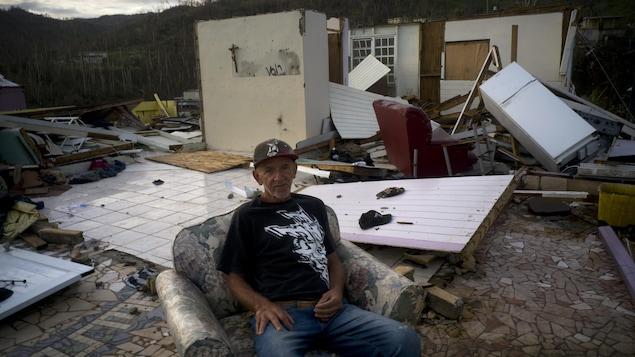Un homme assis dans un fauteuil devant sa maison détruite.
