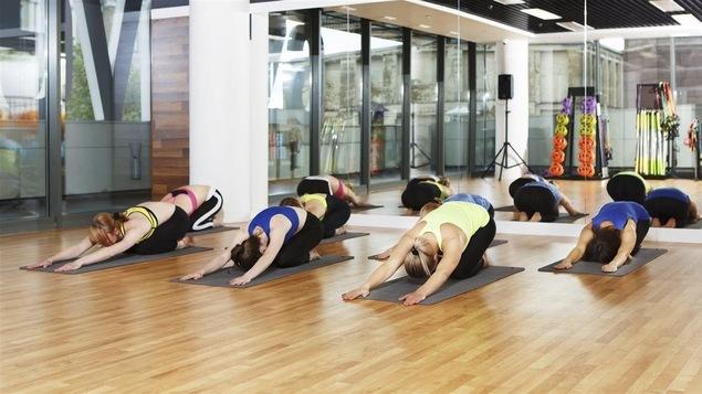 Un groupe de femmes suit un cours de yoga dans une salle de gym.