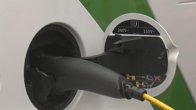 Prise de recharge sur une voiture électrique, la prise de la borne de recharge est insérée dans la prise de la voiture.