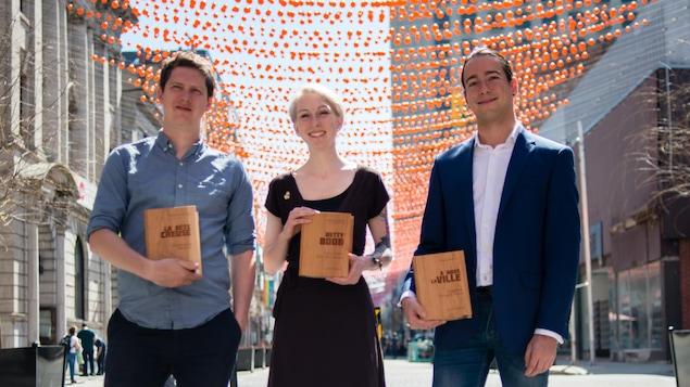 Le romancier Christophe Bernard, la bédéiste Véronique Cazot et et l'essayiste Jonathan Durand prennent la pose, avec leur prix entre les mains, sur la rue Sainte-Catherine, à Montréal, le 9 mai 2018.