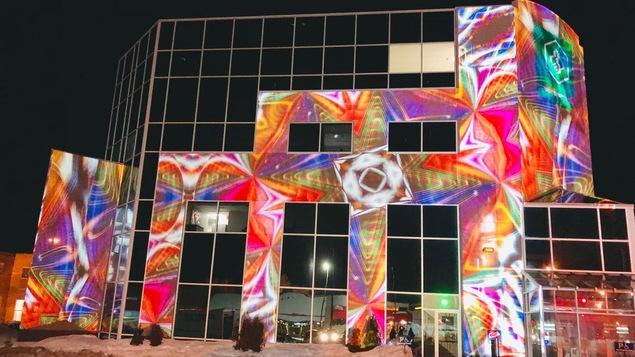 Une projection d'images sur un bâtiment vitré.
