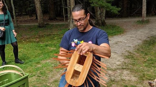 Un homme qui réalise un panier de frêne dans la nature.