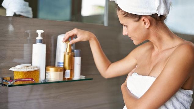 Une femme choisit un produit de beauté dans la salle de bain.