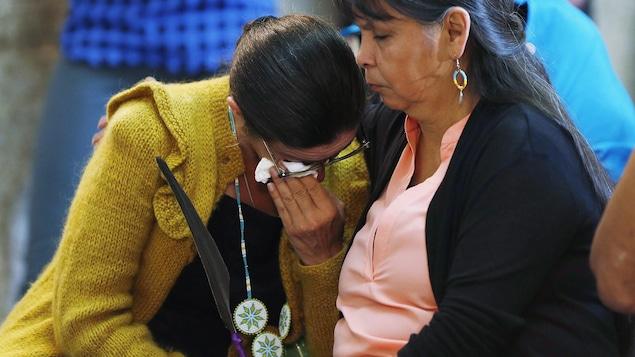 Une femme est réconfortée lors d'un rassemblement des victimes de la rafle des années 1960 avant une excuse provinciale, au Manitoba, en juin 2015.