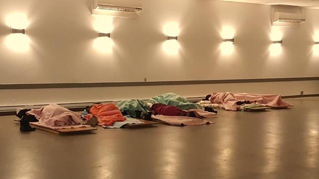 Des réfugiés dorment sur le sol au centre communautaire d'Emerson
