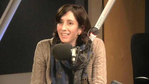 Une jeune dame assise derrière un micro dans un studio radio