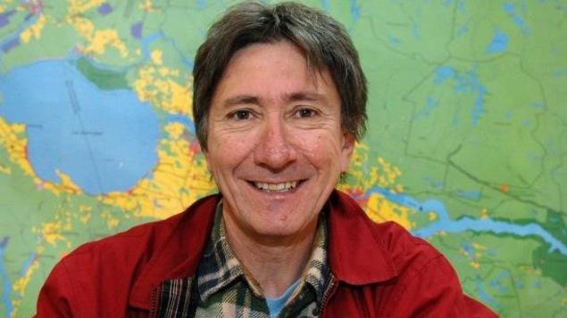 René Tremblay devant une carte du Saguenay-Lac-Saint-Jean