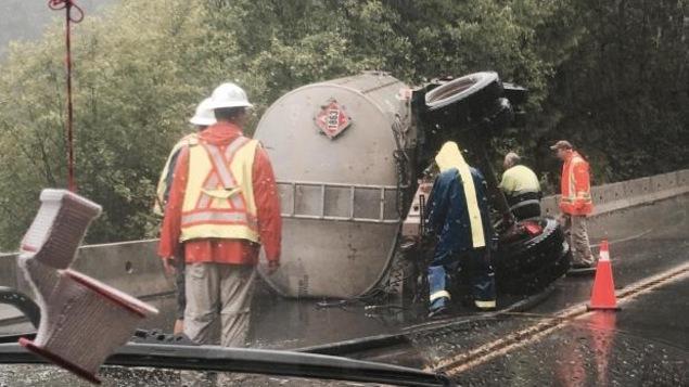 Des travailleurs sont regroupés autour de ce qui ressemble à un morceau de camion renversé.