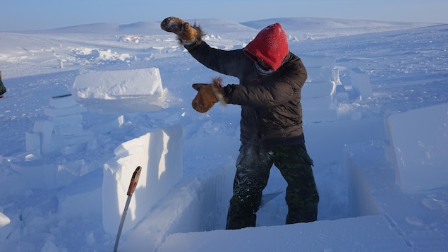 Matthew Manik découpe de la neige pour construire un igloo.