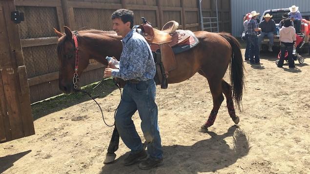 Un cowboy et sa monture s'apprêtent à participer à la finale canadienne de rodéo à Saint-Tite.