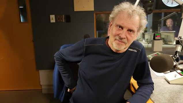 Un homme se tient assis devant un micro.
