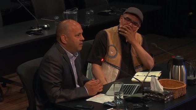 Deux hommes innus assis et parlant dans un micro. L'un porte un veston noire et une blouse mauve, l'autre poste une veste faite par des autochtones qui semble être en peau d'animal et une blouse noire.