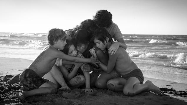 Des enfants blottis les uns contre les autres sur une plage au bord de la mer