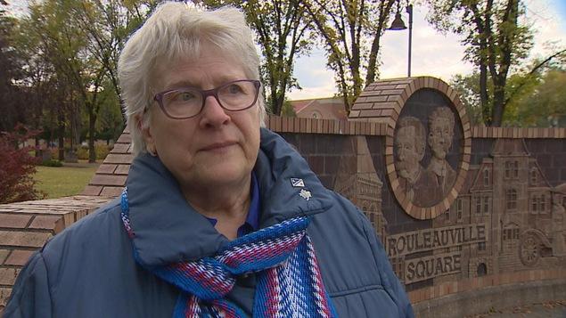 Suzanne de Courville Nicole est devant le parc de Rouleauville. Elle a des cheveux blancs et des lunettes.