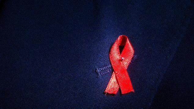 Un ruban rouge, symbole de la lutte au sida et au VIH, épinglé sur une veste.