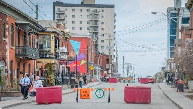 Des pots de fleurs et des barrières délimitent la portion piétonne de la rue.
