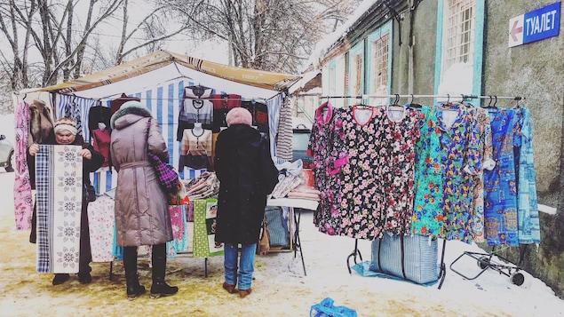 Des femmes portant des manteaux regardent des vêtements présentés à l'extérieur d'un bâtiment pour être vendus.