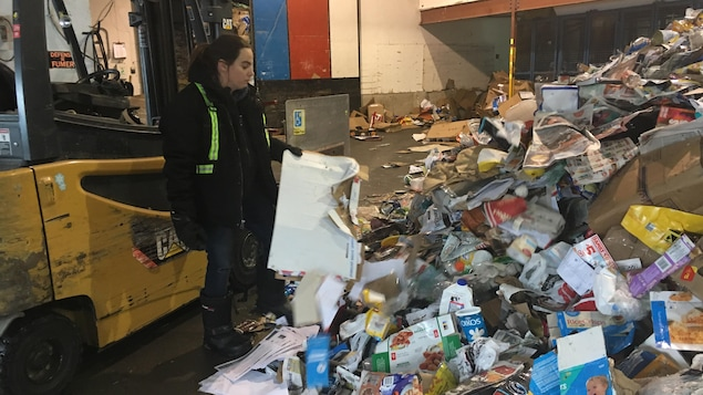 Une employée dans le centre de tri examine des déchets domestiques.