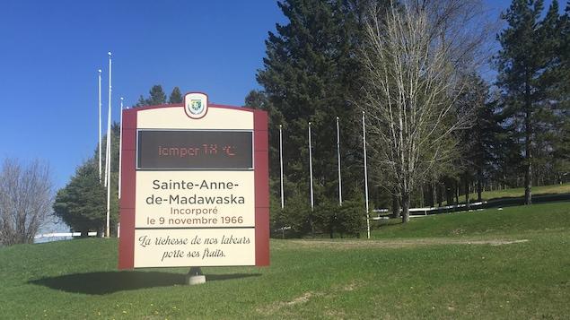 Dans un parc, l'enseigne à l'effigie du village de Sainte-Anne-de-Madawaska sur laquelle on peut lire : Incorporé le 9 novembre 1966. Le slogan du village : « La richesse de nos labeurs porte ses fruits ».