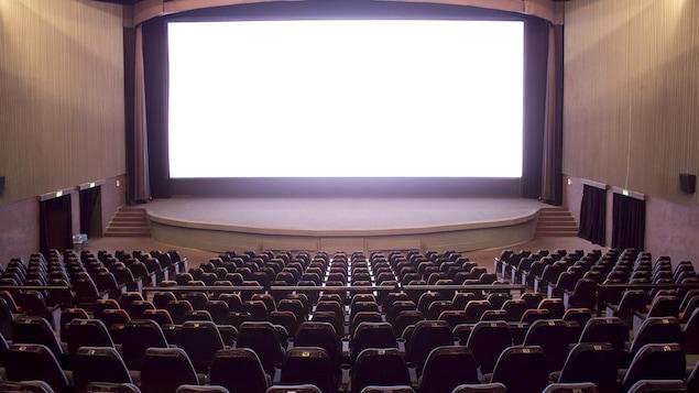 Une salle de cinéma avec un écran blanc en arrière plan.