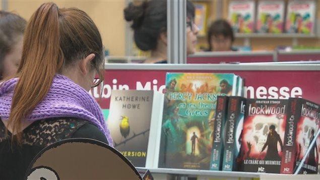Une jeune femme devant un présentoir de livres