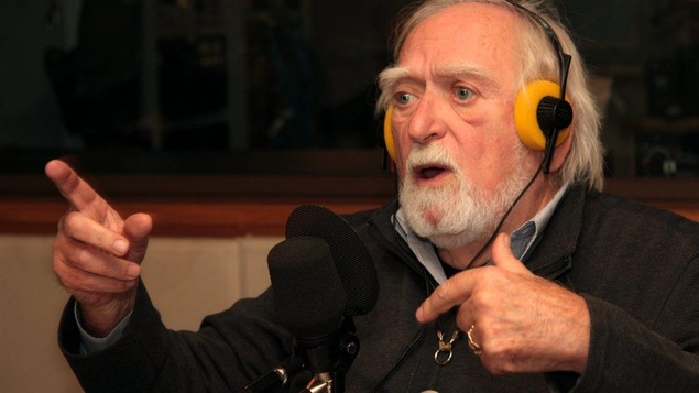 Jacques Languirand avec des écouteurs sur la tête pointe du doigt, dans un studio de radio de Radio-Canada.