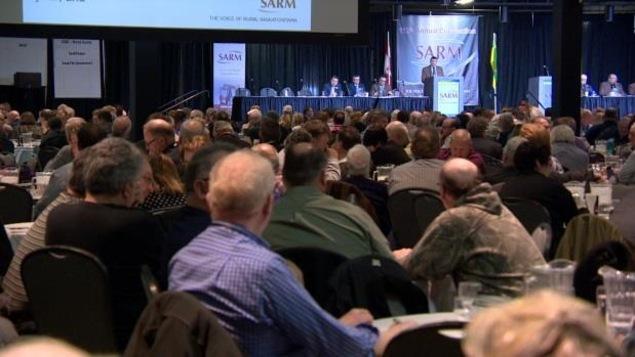 Un public assis écoute un conférencier qui s'adresse à lui dans une grande salle.