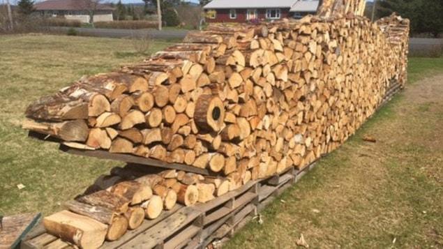Brian Golding empile son bois de façon à en faire une oeuvre d'art à Pennfield