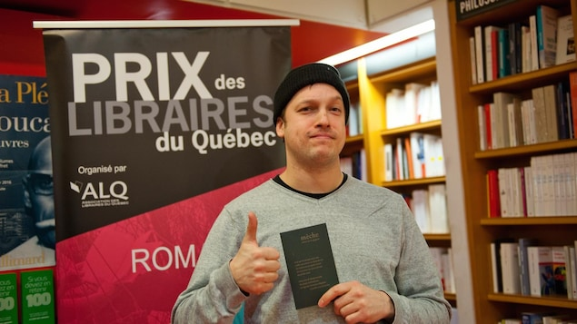 Sébastien B. Gagnon, le lauréat du Prix des libraires du Québec  2017, catégorie poésie québécoise, pose avec son recueil « mèche » (L'Oie de Cravan)