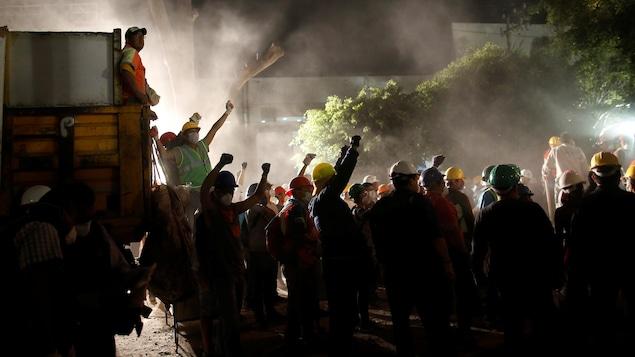 Des secouristes à l'oeuvre à Mexico lèvent le poing pour imposer le silence, dans l'espoir d'entendre des survivants dans les décombres.