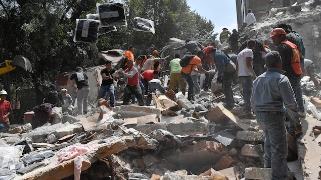 Des gens retirent des débris d'un bâtiment, qui s'est effondré après le séisme de magnitude 7,1 survenu mardi, à la recherche de victimes éventuelles.