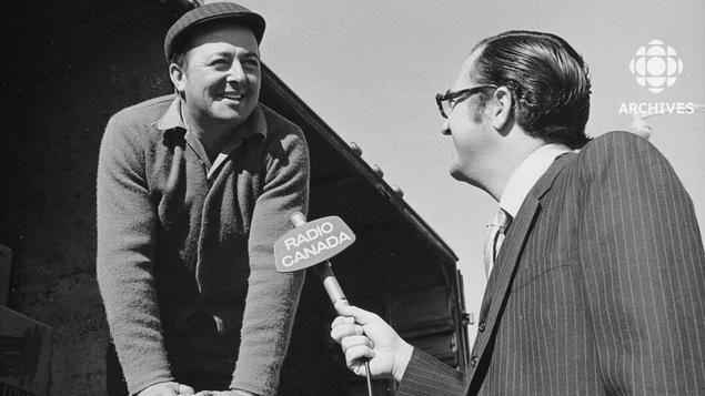 Journaliste qui tient un micro en entrevue avec un producteur qui est appuyé sur un sac d'oignons.