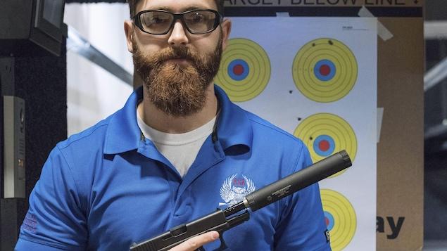 Un membre du Groupe américain pour les silencieux pose avec son arme.