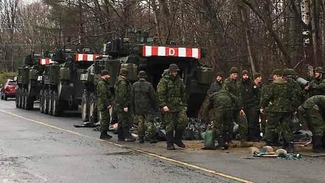 Des membres des Forces armées canadiennes en bordure d'une route.