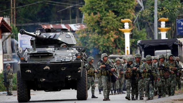 Des soldats philippins progressent dans une rue de Marawi sous la protection d'un blindé léger,