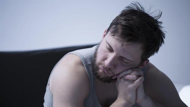 Un homme s'endort assit, la tête posée sur ses mains.
