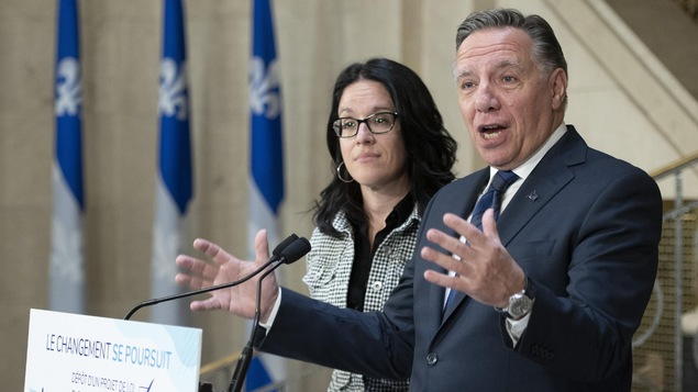 François Legault et Sonia LeBel s'adressent aux médias debout derrière une tribune.