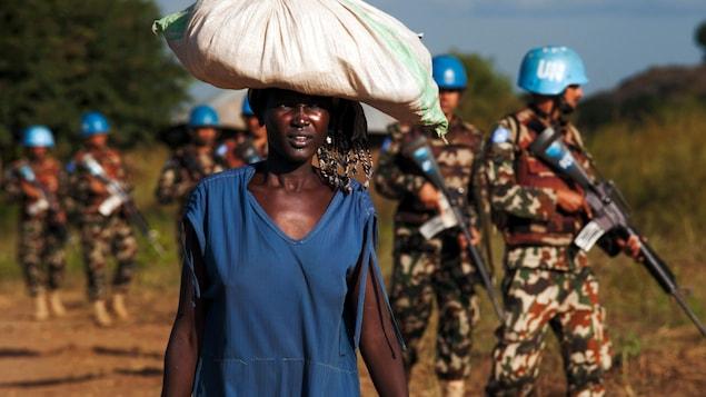 Une déplacée transporte des vivres pendant que des Casques bleus de l'ONU patrouillent le site de la ville de Juba, en octobre 2016.