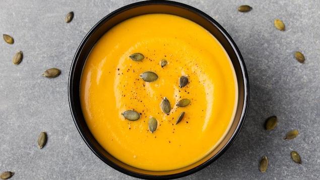 Un bol de soupe de courge parsemé de sel, de poivre et de graines de courge