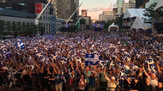 Des milliers de personnes brandissent leurs drapeaux québécois durant le spectacle de la Fête nationale du Québec à Montréal, sur la place des Festivals, le 23 juin 2016.