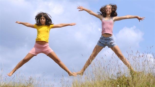 """Deux jeunes filles sautent dans un champ d'herbe en faisant des """"jumping jack""""."""