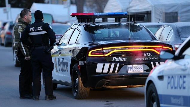 Des policiers discutent près d'une autopatrouille.