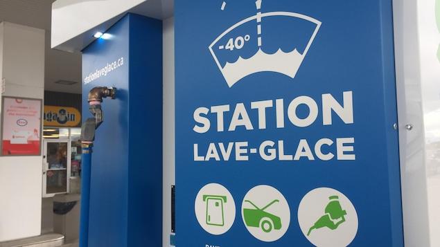 Une pompe, bleue, avec des pictogrammes et les inscriptions : « Station lave-glace », « payez », « ouvrez » et « remplissez ».